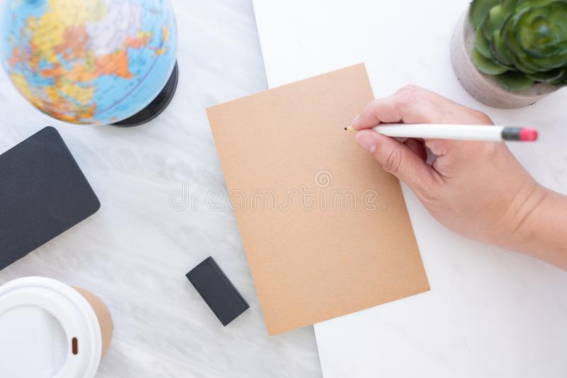 Hand holding pen writing on brown paper with blue globe,blackboard,coffee cup on marble table.new year's resolutions stock photo
