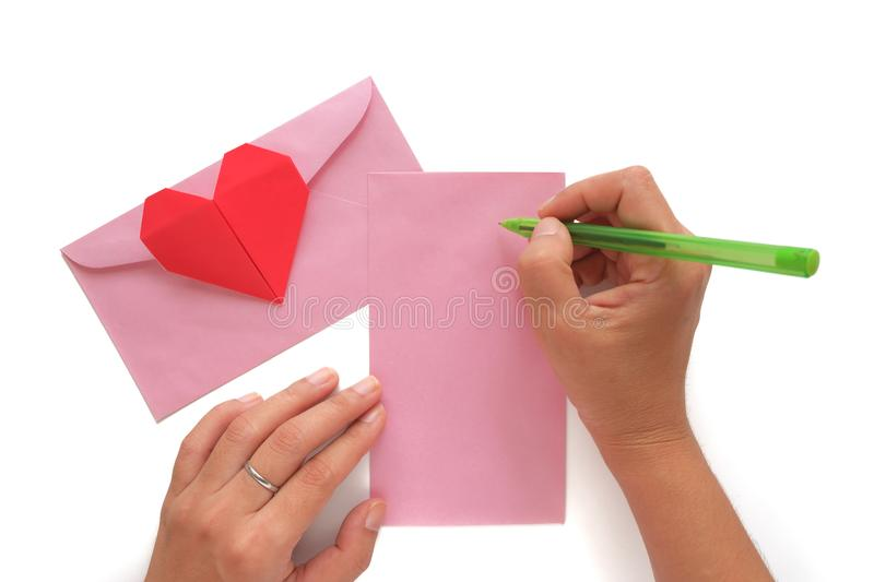 Hand holding a pen and writing a letter with red heart paper origami and pink envelope royalty free stock image