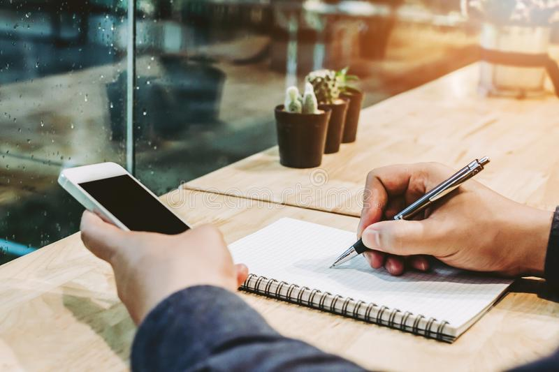 Hand holding pen writing on paper note,shopping online on mobile phone in coffee shop with cactus on table. Hand holding pen writing on paper note,shopping royalty free stock photography