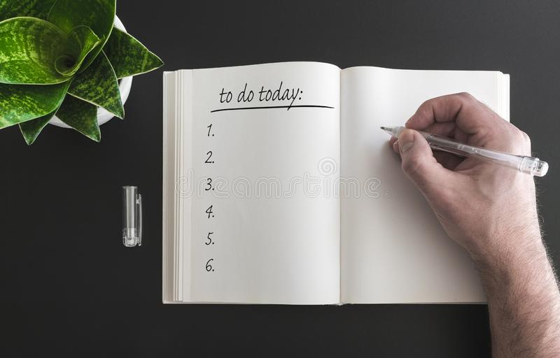 Hand holding pen writing to do list in open book on desk royalty free stock photo