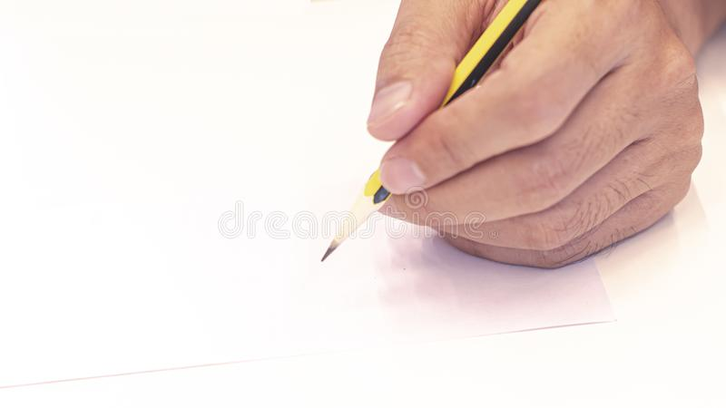 Hand holding a pencil  on white background . Close Up on a man`s hand writing on paper with a pencil  .Planning business stock images