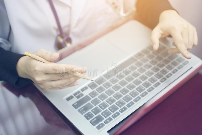 Hand holding pencil of woman doctor and finger pointing the screen of laptop to explain something for working at hospital stock photo