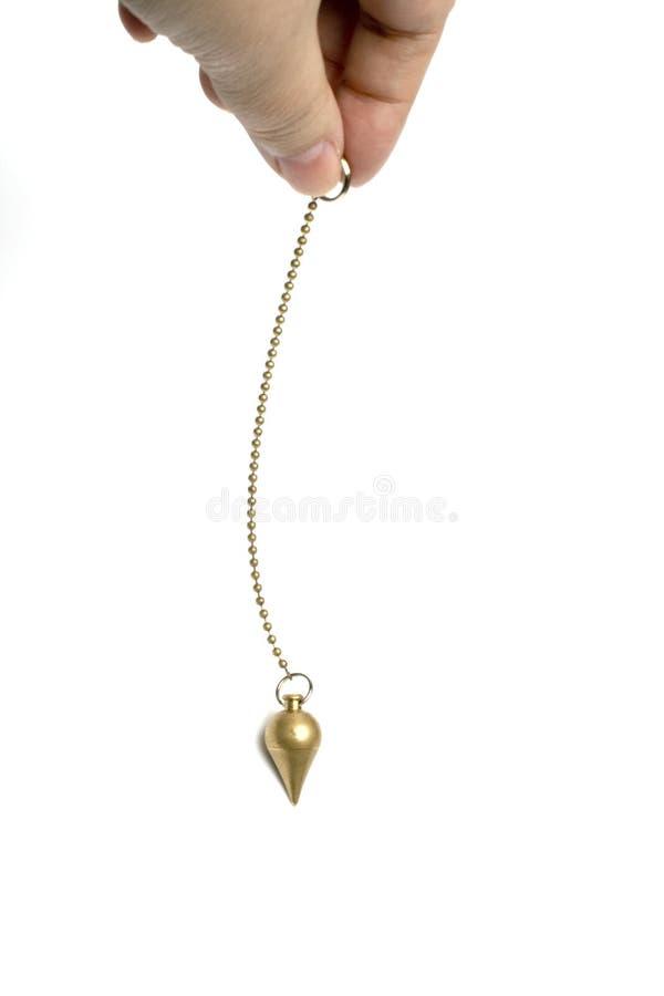 Hand holding a pendulum royalty free stock image