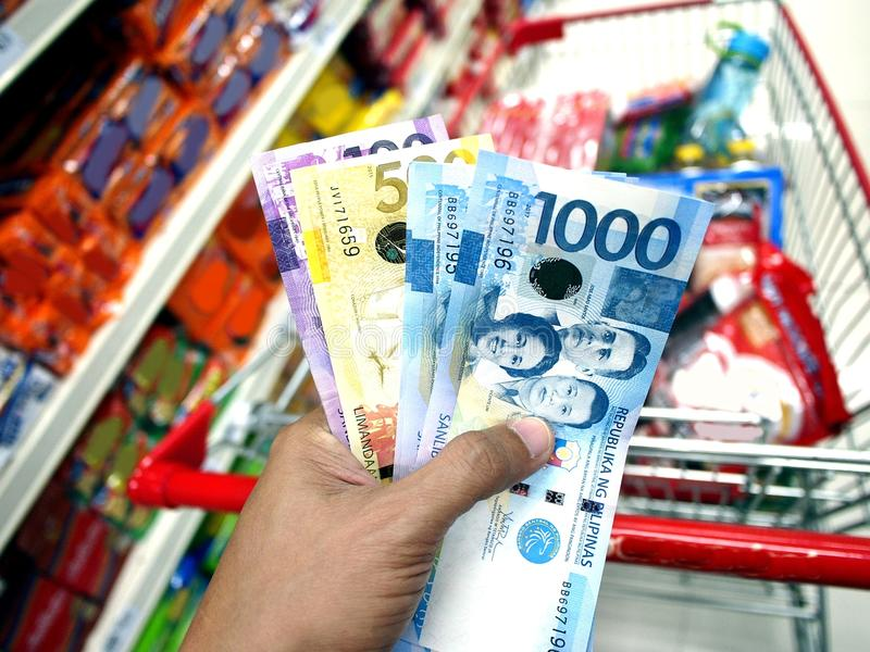 Hand holding Philippine Peso bills. Photo of a hand holding Philippine Peso bills while inside a grocery store stock photos