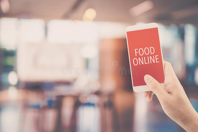 Hand holding phone with food order online with blur of restaurant background. Hand holding phone with food order online with blur of restaurant background stock image