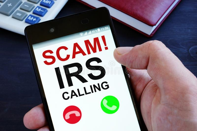 Hand is holding phone with irs scam calls. Hand is holding smartphone with irs scam calls stock photos