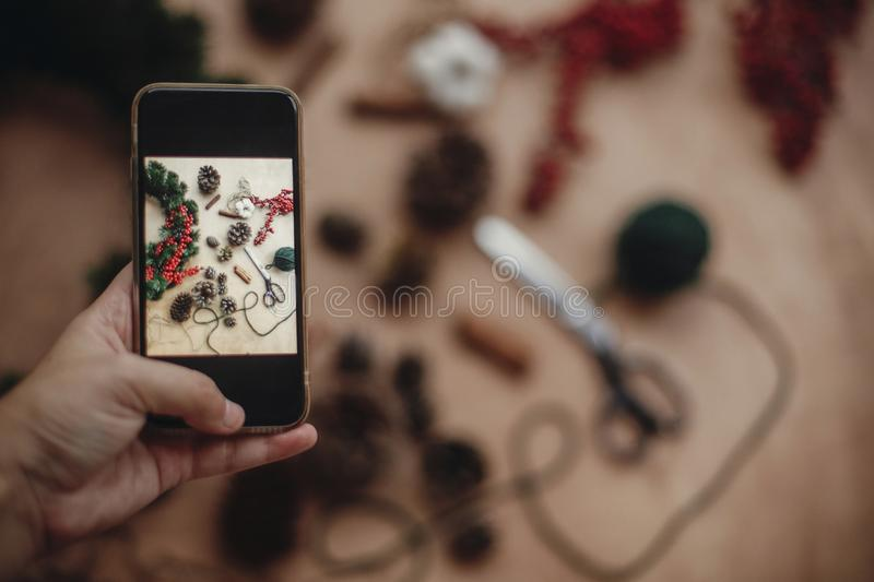Hand holding phone and taking photo of rustic christmas wreath f stock photos