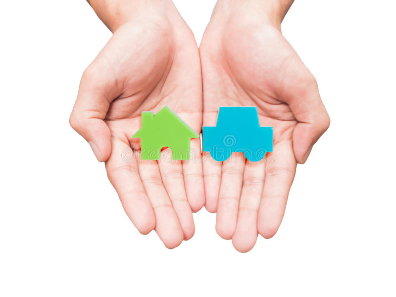 Hand holding piece of car and house model. Two hands holding green house and blue car model isolated on white background stock photography