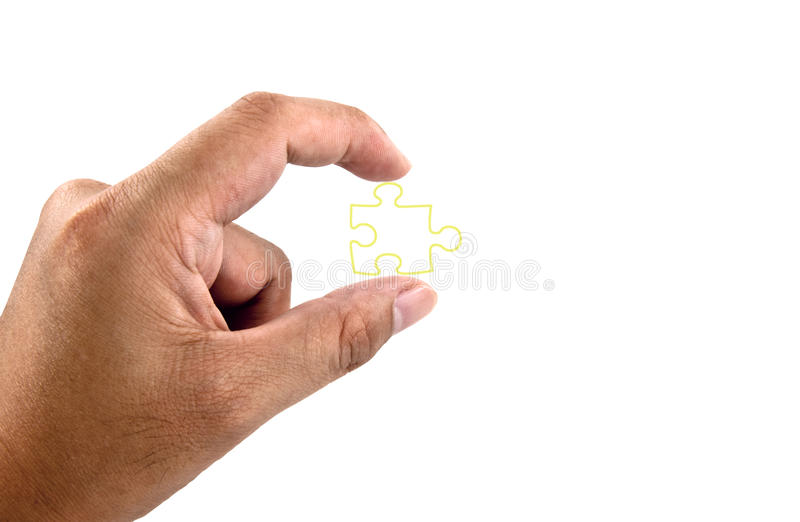 Hand holding piece of jigsaw. A hand holding a jigsaw piece isolated against a white background stock photo