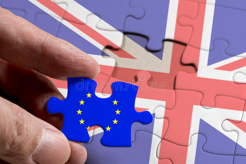 Hand holding piece of jigsaw puzzle with flag of European Union royalty free stock photos