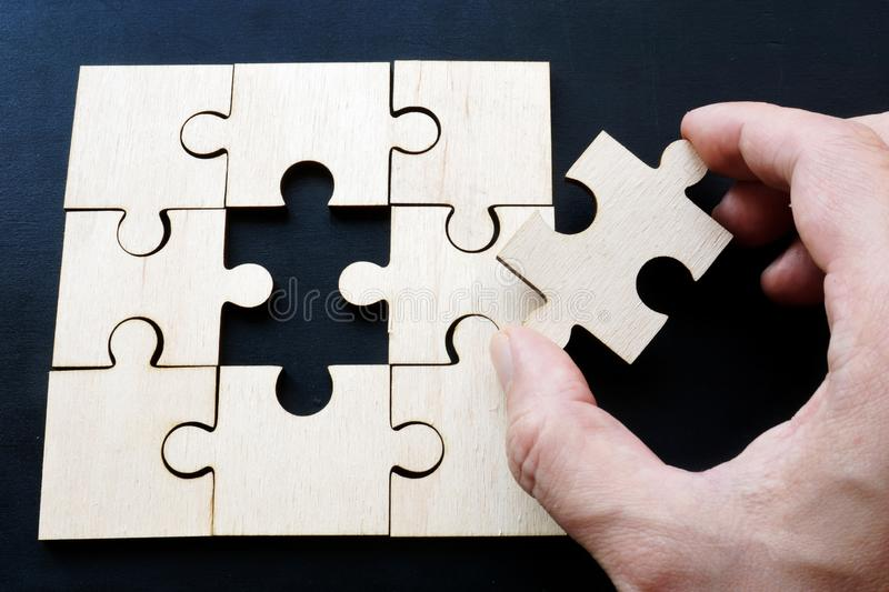 Hand is holding piece of jigsaw puzzle. Problem solving in business. royalty free stock images