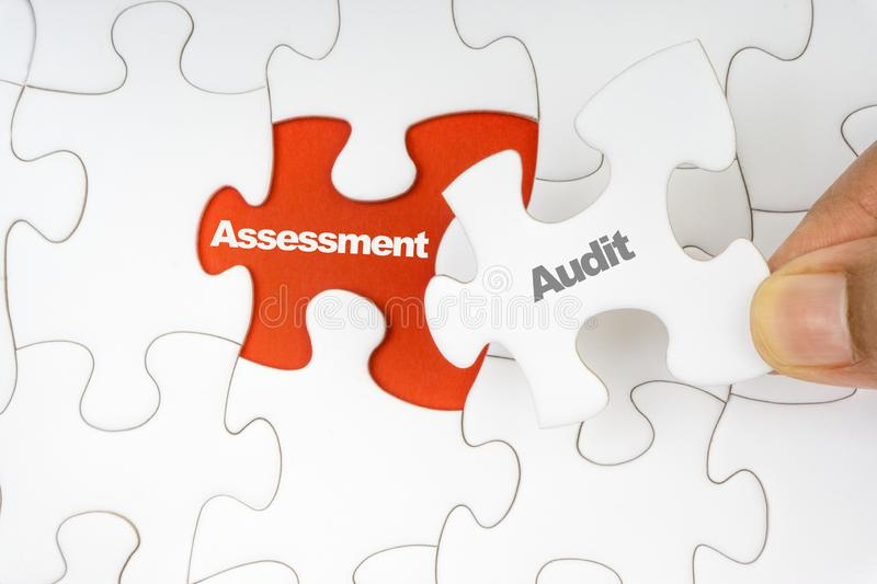 Hand holding piece of jigsaw puzzle with word AUDIT ASSESSMENT royalty free stock image