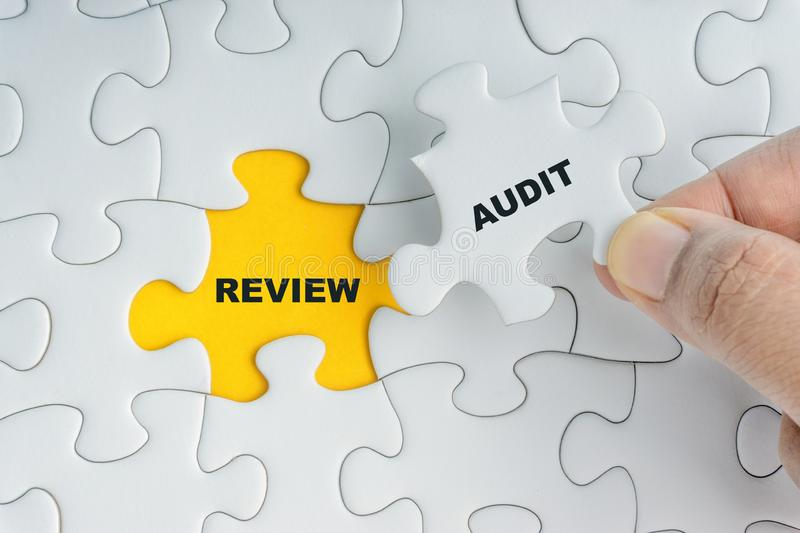 Hand holding piece of jigsaw puzzle with word AUDIT REVIEW. Selective focus stock photos