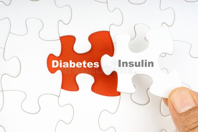 Hand holding piece of jigsaw puzzle with word DIABETES INSULIN royalty free stock photo