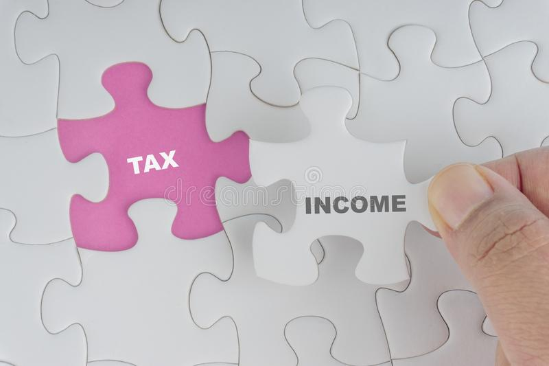 Hand holding piece of jigsaw puzzle with word INCOME TAX. royalty free stock photo