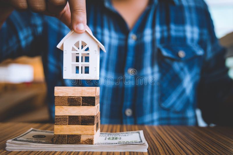 Hand holding a piece of wood block with model white house on dollar banknote. Insurance and property investment real estate. Concept stock photography