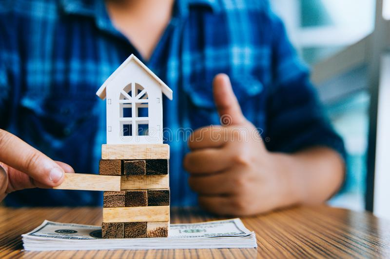 Hand holding a piece of wood block with model white house on dollar banknote. Insurance and property investment real estate. Concept stock photo