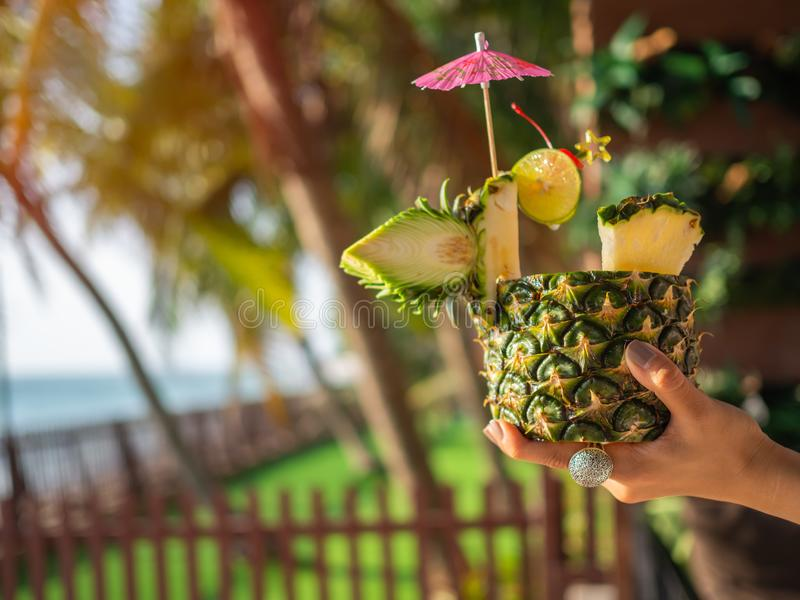 Hand holding pineapple juice cocktail near the beach in summer royalty free stock images