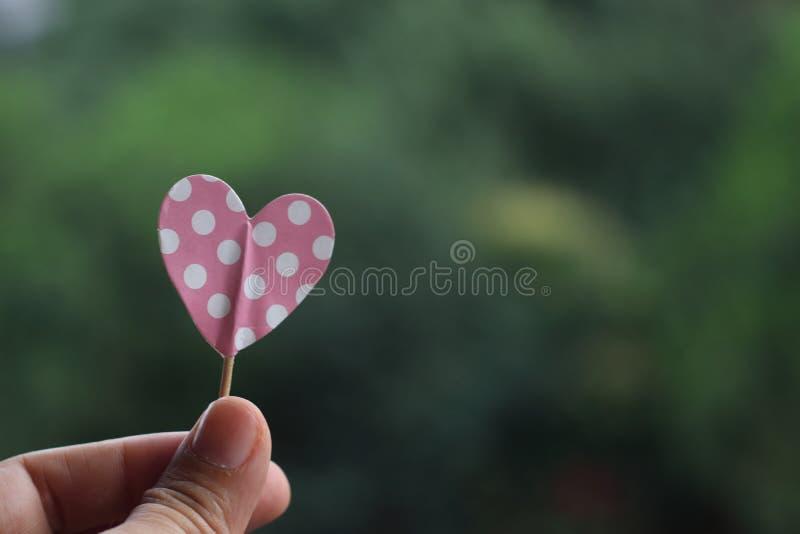 Hand holding pink polka dot paper heart stock photo