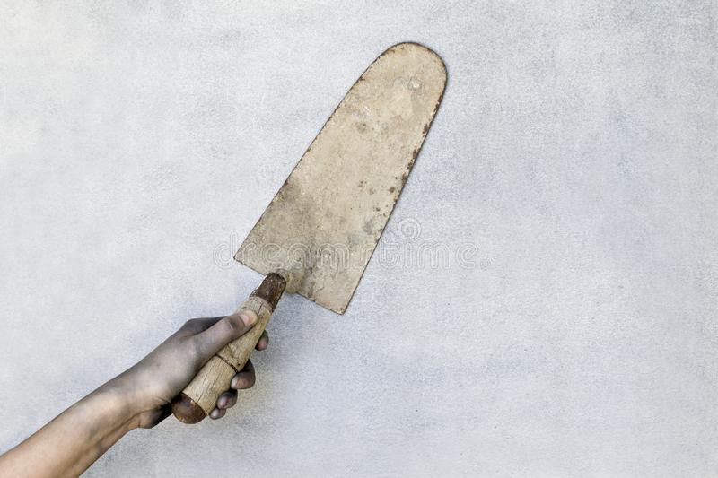Hand holding a plaster trowel on gray background. royalty free stock photography