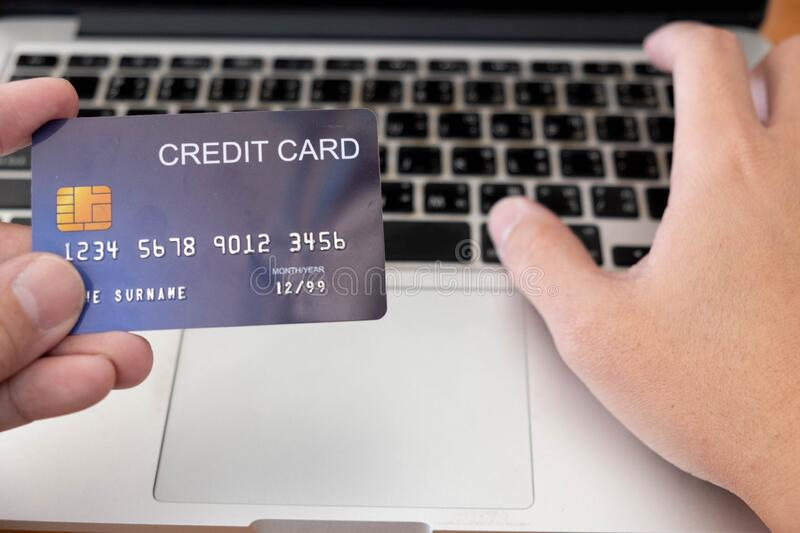 The Hand holding plastic credit card and other hand pressing keyboard on laptop for online shopping. Online shopping concept. Hand holding plastic credit card stock photo