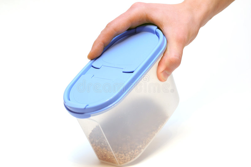Hand holding plastic food container isolated. Hand with transparent plastic food container with grain isolated on white background royalty free stock image