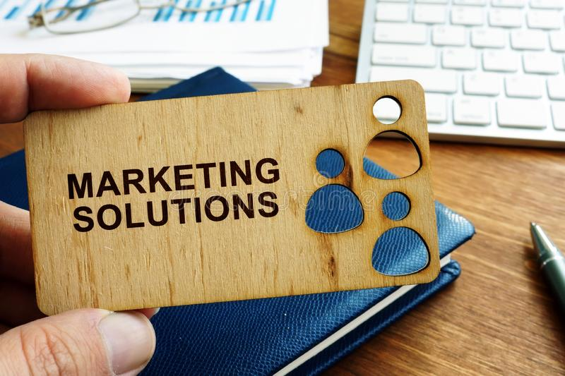Hand holding plate with marketing solutions stock photography
