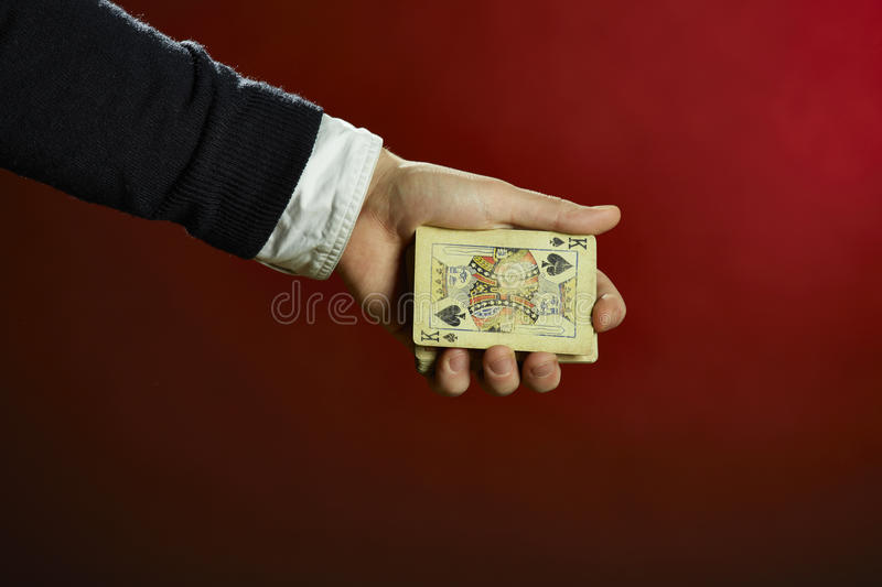 Hand holding playing cards. Male hand holding playing cards over red background stock photo