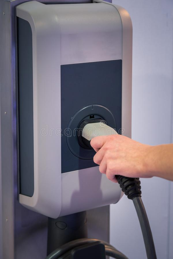 Close up of female hand holding electric car charger stock photography