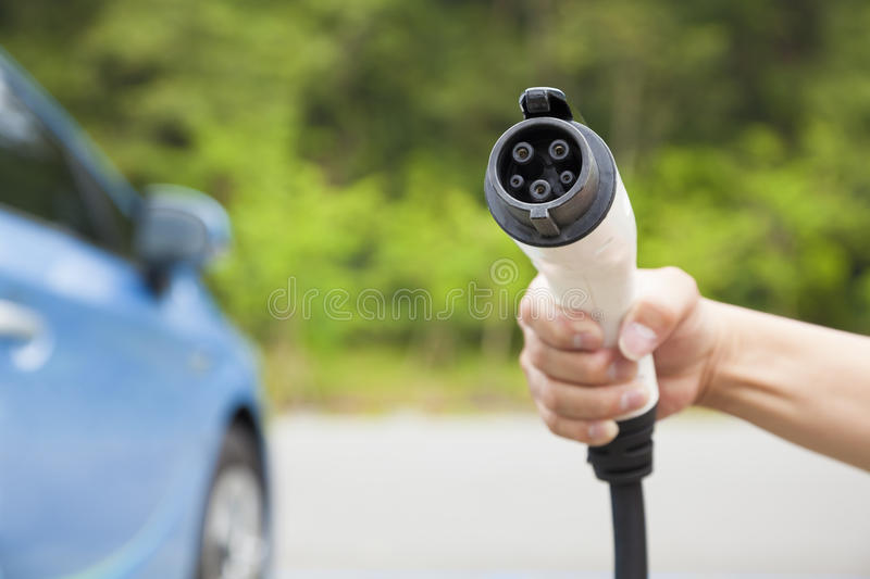 Hand holding plug in connector for Charging electric car. Eco energy concept royalty free stock photos
