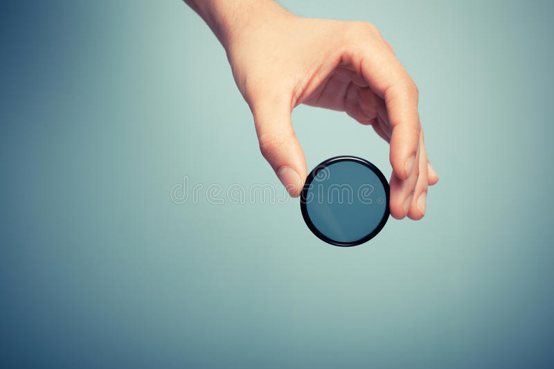 Hand holding polarizer filter. A hand is holding circular polarizer filter royalty free stock photography