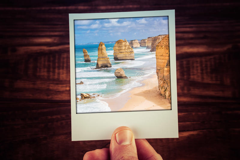 Hand holding polaroid photograph of The Twelve Apostles, Great O. Cean Road, Australia with copy space. Travel memories of good old times royalty free stock photos