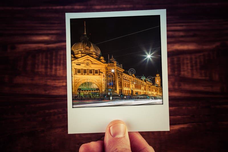 Hand holding polaroid postcard of Flinders Street Station at night. Melbourne, Australia. Travel memories scrapbooking of good ti stock image