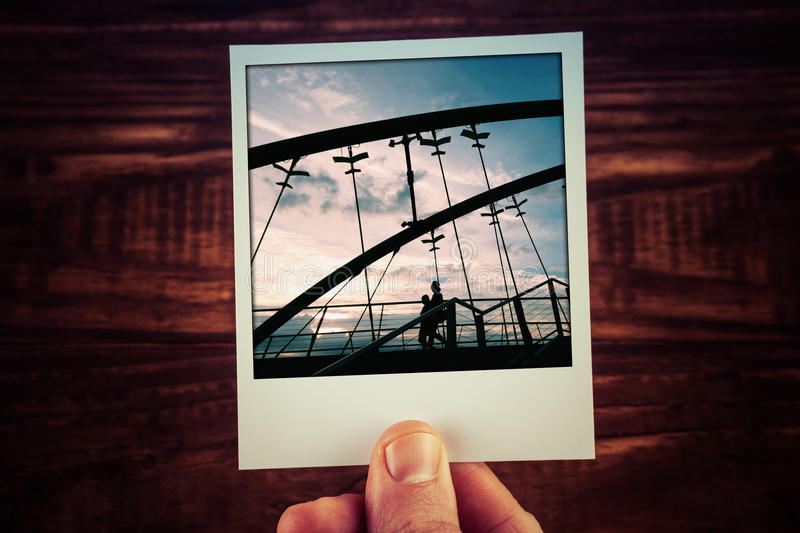 Hand holding polaroid postcard of two people silhouettes walking. On Frankston Bridge at sunset. Travel memories scrapbooking template with copy space stock images