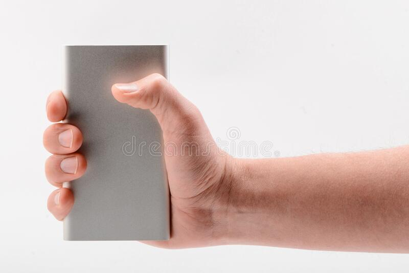 Hand holding a power bank on white background royalty free stock images