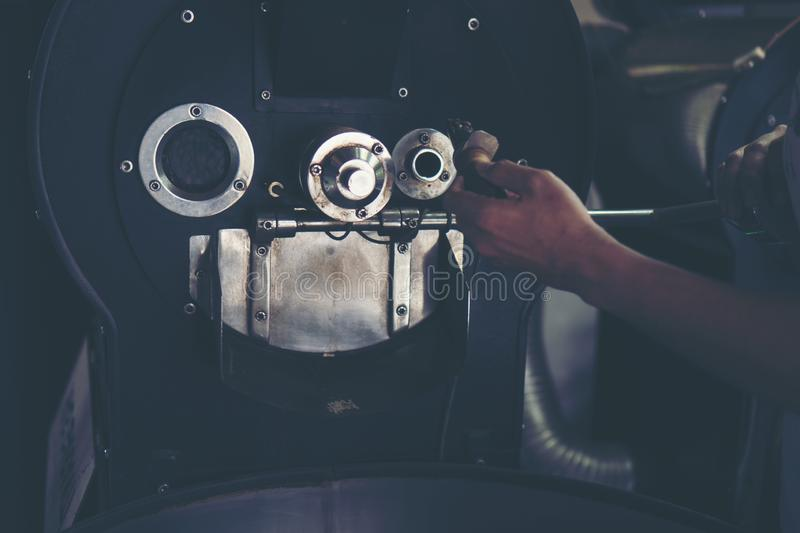 Hand holding a probe of fresh roasted coffee beans in vintage co. Hand holding a probe of fresh roasted coffee beans in vintage filter image stock image