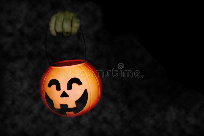 Hand holding a pumpkin of halloween baubles royalty free stock images