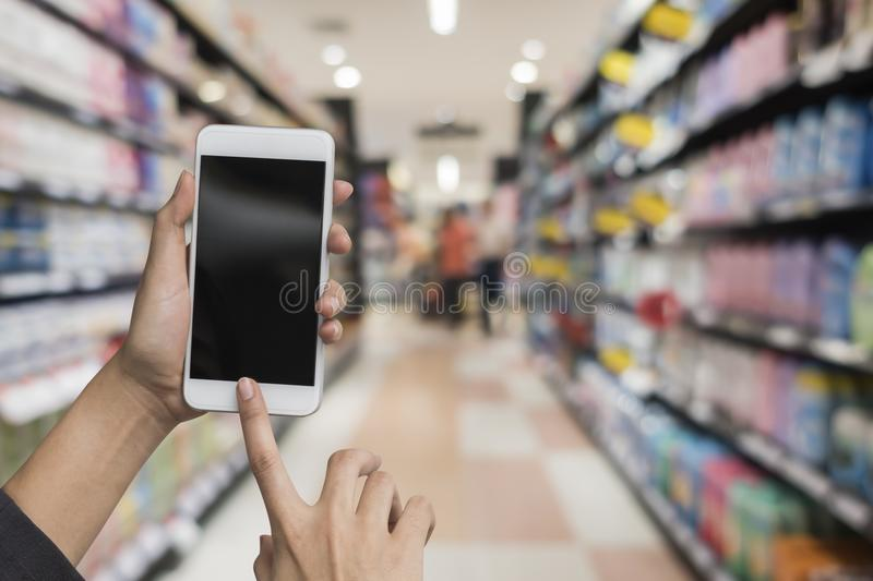 Hand holding and pushing smart phone. On blurred in deparment store royalty free stock image