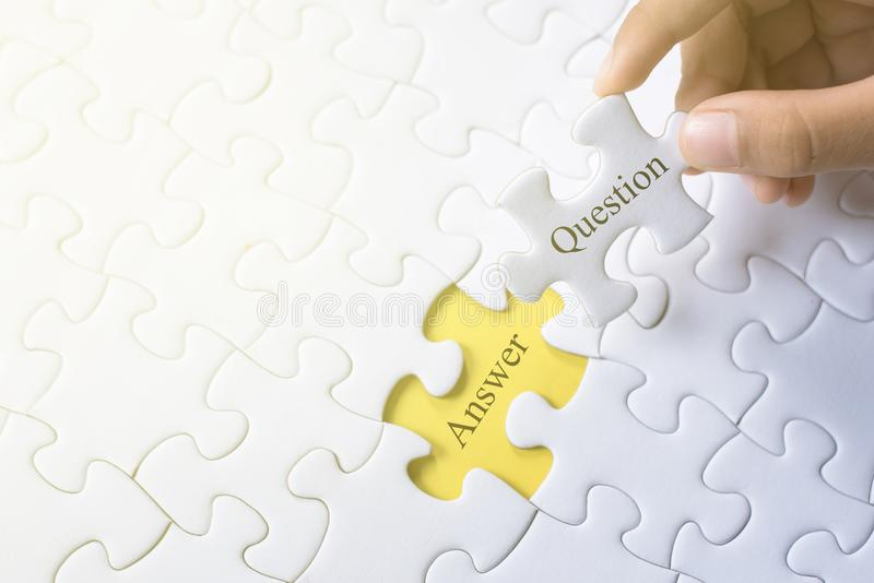 Hand holding question and answer word on jigsaw puzzle. Q&a, faq and question concept stock photography