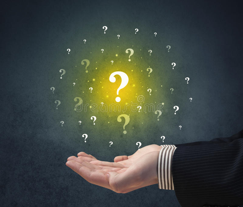 Hand holding question marks. Yellow question marks hovering over young hand royalty free stock photos