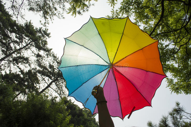 Hand holding a rainbow umbrella. ,Rainbow distraction can effectively block the sun umbrella royalty free stock photo
