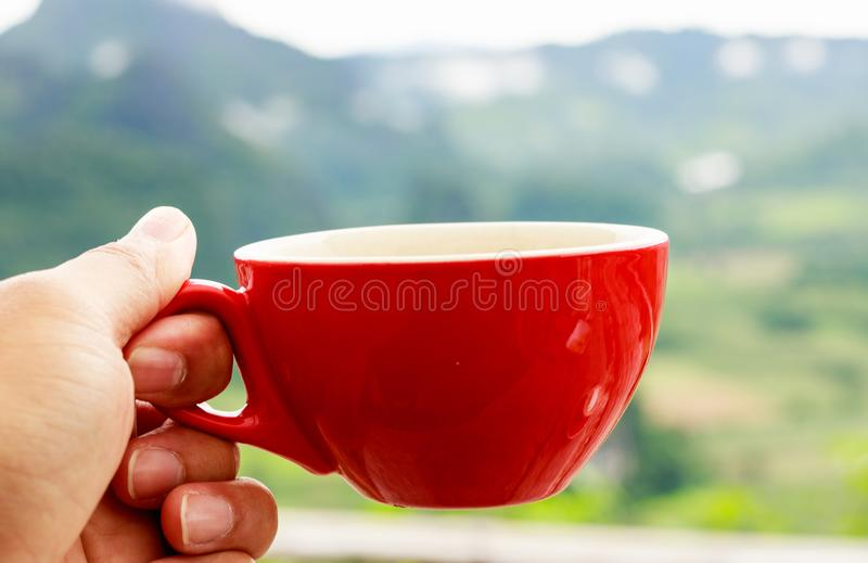 Hand holding a red cup of coffee with blurred mountain background in morning time. royalty free stock images