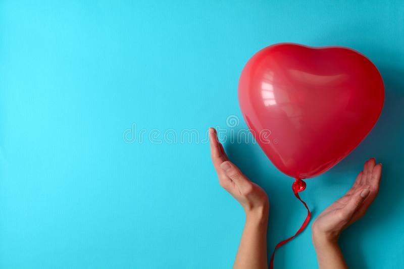 Hand holding a red heart balloons on blue paper background. Valentine`s day or birthday celebration concept royalty free stock photo