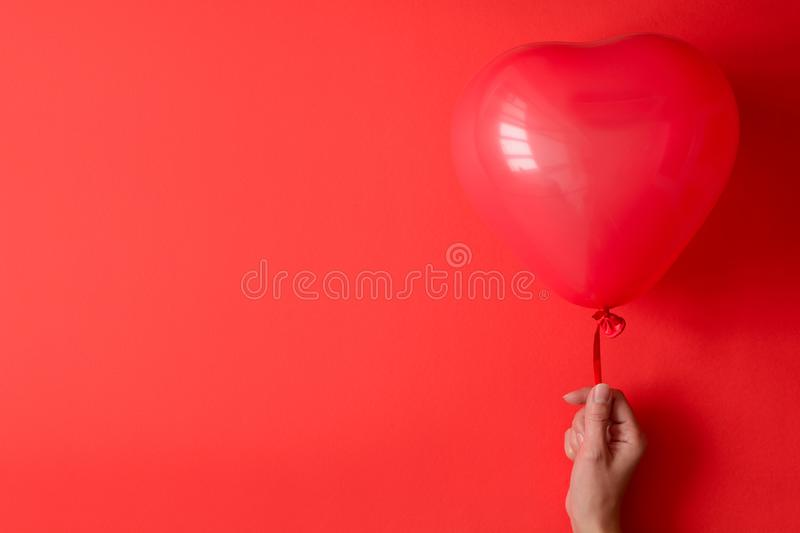Hand holding a red heart balloons on red paper background. Valentine`s day or birthday celebration concept royalty free stock images