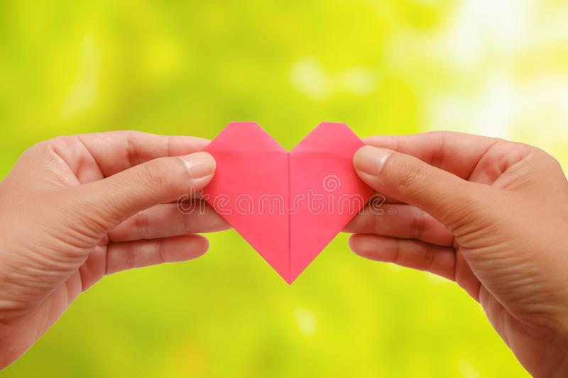 Hand holding red heart paper origami on blurred green natural ba stock image