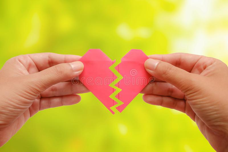 Hand holding red paper broken heart on blurred green natural background stock photos