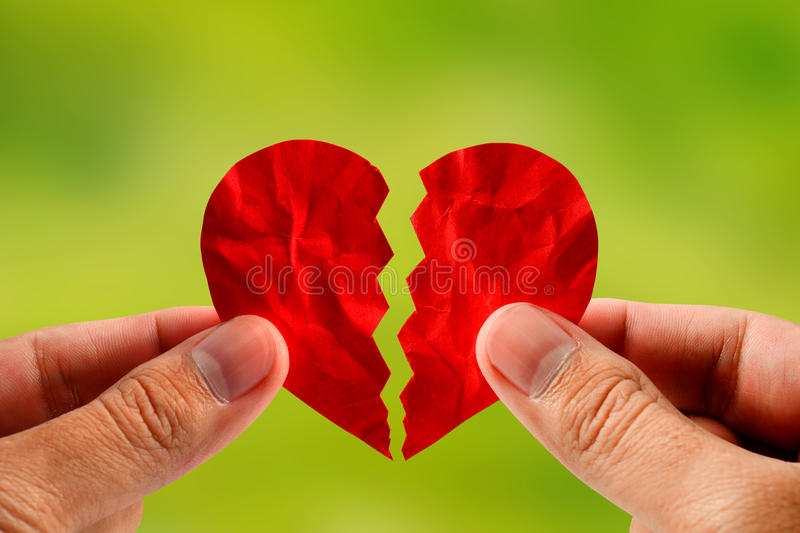 Hand holding red paper broken heart for divorce or reconcile. Hand holding a red paper broken heart for divorce or reconcile with nature background royalty free stock image