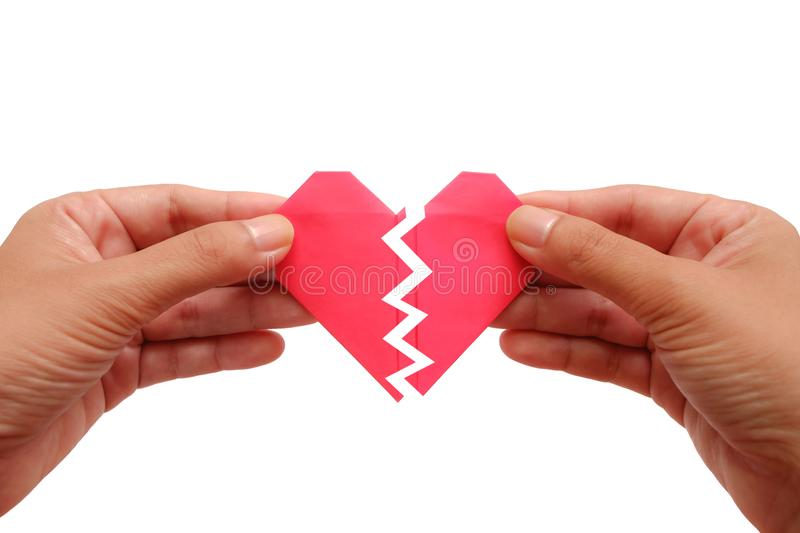 Hand holding red paper broken heart on white background stock image