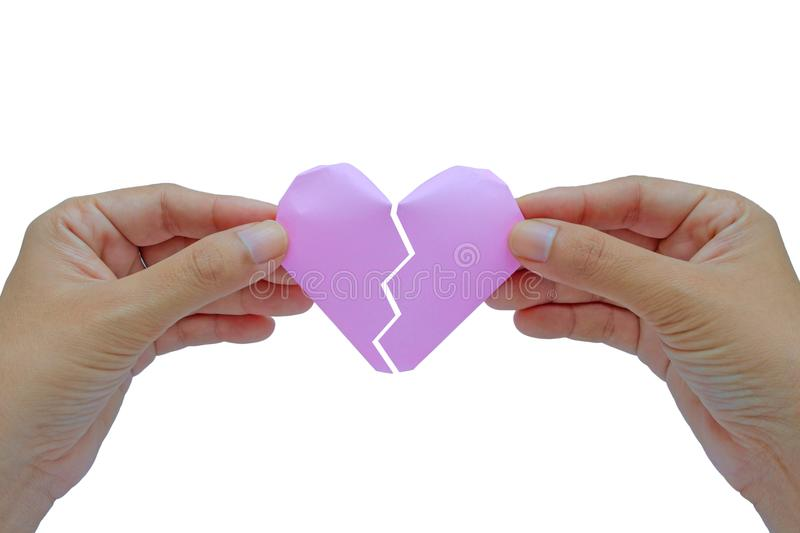 Hand holding red paper broken heart on white background royalty free stock photography