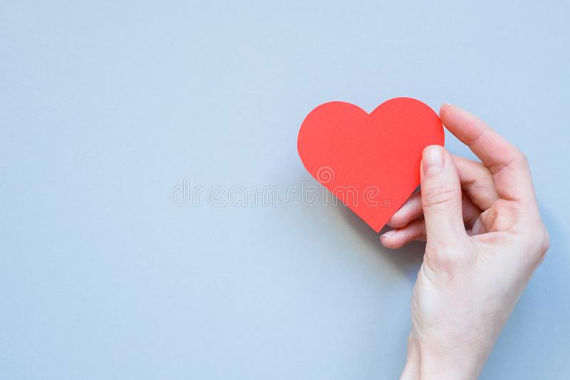 Hand holding red paper heart on the blue background. With copy space stock image